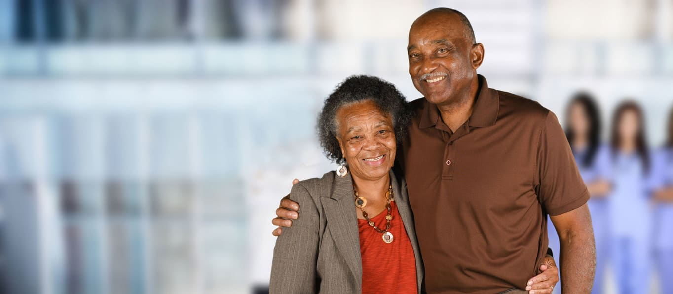 Elderly african american couple standing with arms around each other